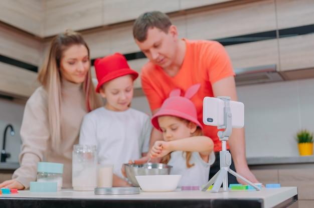 Maman avec son père apprend à deux filles à faire cuire de la pâte dans la cuisine.