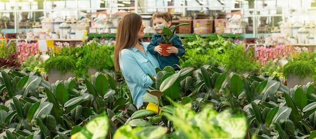 Maman et son petit garçon dans un magasin de plantes choisissent des plantes. jardinage en serre. jardin botanique, floriculture, concept de l'industrie horticole