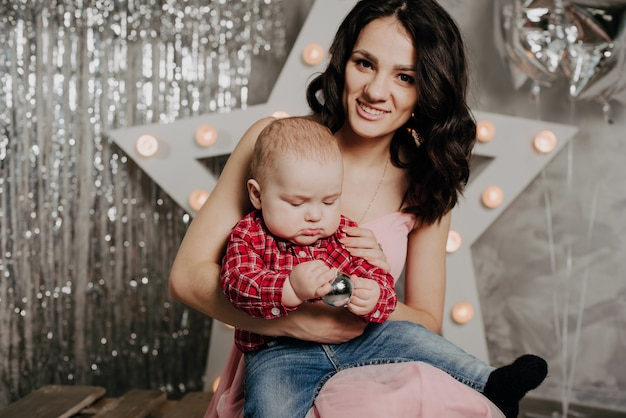 Maman avec son petit garçon nouveau-né dans ses bras, décor de noël