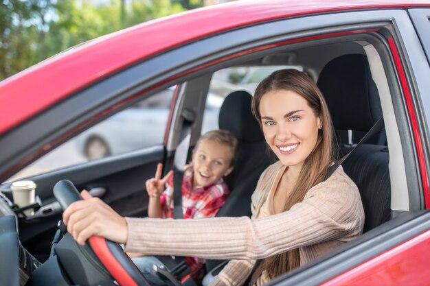Maman souriante au volant avec sa fille, montrant le signe de la paix depuis le siège passager