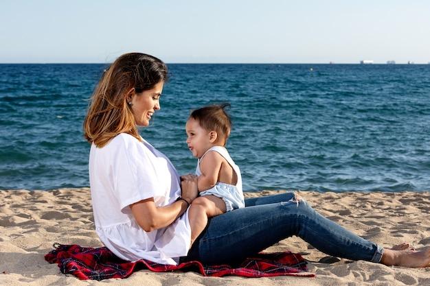 Maman souriante jouant avec un nouveau-né allongé sur une serviette de plage