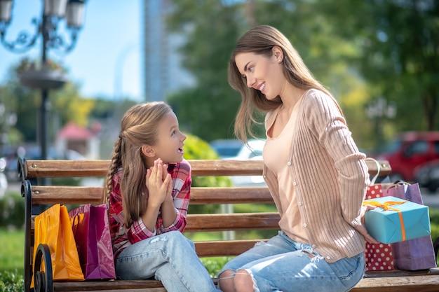 Maman souriante présentant sa boîte-cadeau fille surprise sur banc de parc