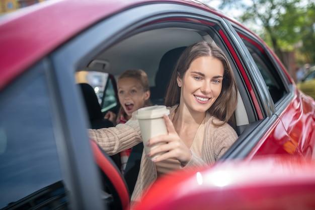Maman souriante tenant une tasse de café, conduisant avec sa fille étonnée