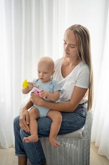 Maman tenant l'enfant à la maison pendant la quarantaine