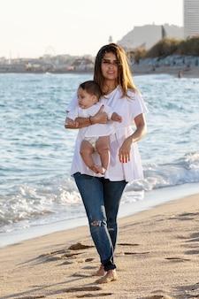 Maman tenant son fils vers le ciel bleu en marchant sur la plage