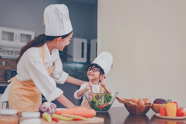 Maman thaïlandaise et enfant cuisinent ensemble à la maison. distanciation sociale et restez à la maison restez en sécurité. activité familiale effet de covid-19 et arrêt du virus de l'épidémie. verrouillage et auto-quarantaine à la maison.