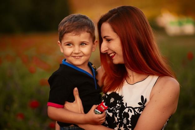 Maman tient un charmant petit fils debout sur le champ vert avec des coquelicots