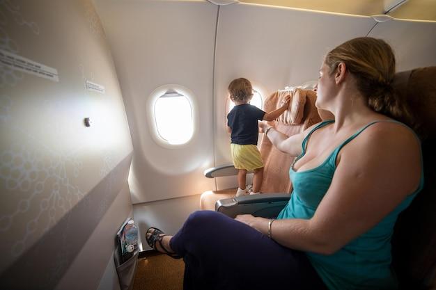 Maman tient un petit enfant dans l'avion avec sa main dangereuse