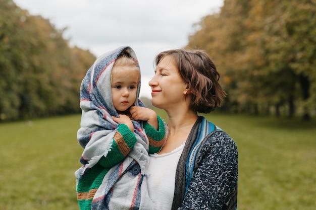 Maman tient sa fille dans ses bras dans le parc. femme avec un petit enfant marche dans le parc en automne. automne.
