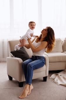 Maman tient sa petite fille dans ses bras. femme heureuse avec un enfant souriant et embrassant son bébé.