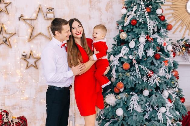 Maman tient son fils dans ses bras et les parents le regardent. famille heureuse près de l'arbre de noël.