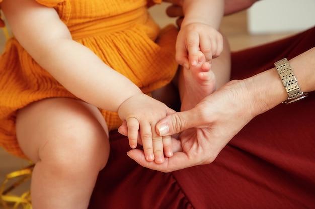 Maman tient le stylo d'un petit enfant dans ses bras en gros plan
