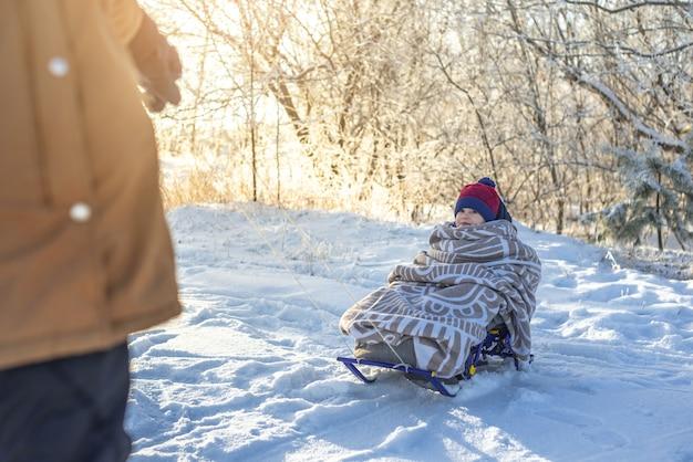 Maman tire un enfant sur un traîneau marchant sur une journée ensoleillée d'hiver glacial à l'extérieur