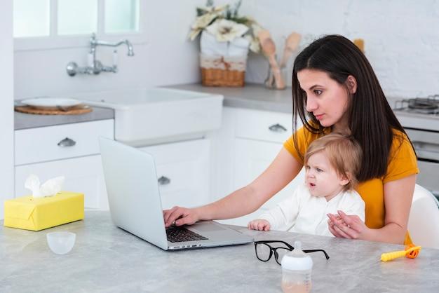 Maman travaille sur un ordinateur portable en tenant bébé