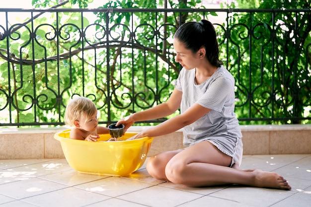 Maman verse d'une louche une petite fille dans un bassin sur le balcon