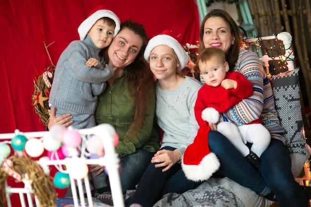 Les mamans avec des enfants accrochés dans un lit décoré pour noël