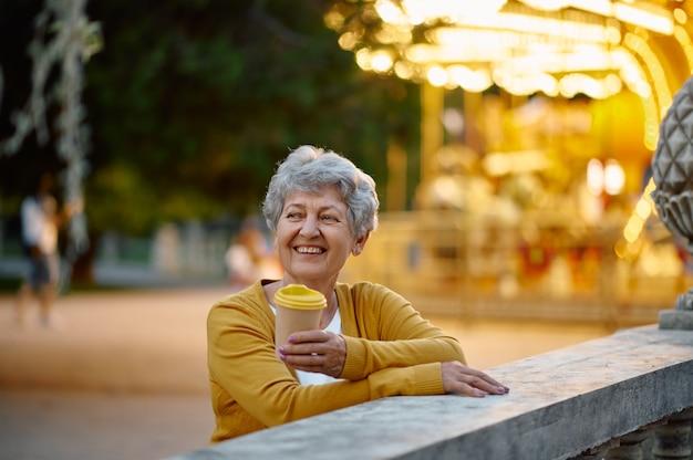 Mamie boit du café dans un parc d'attractions d'été