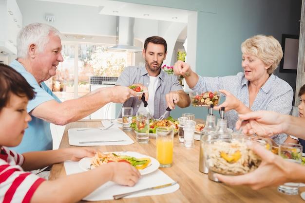 Mamie donnant à manger à grand-père assis à la table à manger