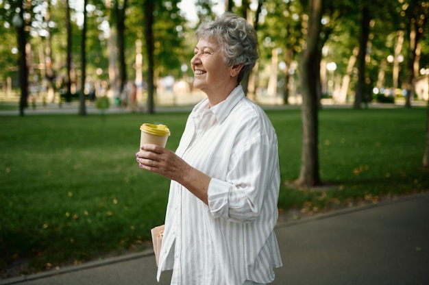 Mamie drôle boit du café dans le parc d'été. mode de vie des personnes âgées. jolie grand-mère s'amusant à l'extérieur, vieille personne de sexe féminin en plein air