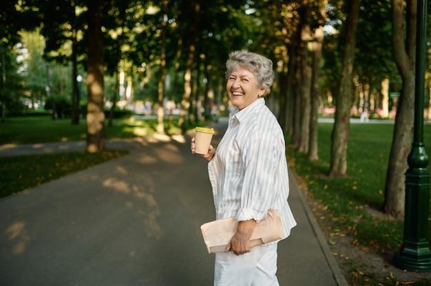 Mamie drôle boit du café dans le parc d'été