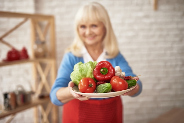 Mamie souriante détient les légumes frais cultivés à la maison.