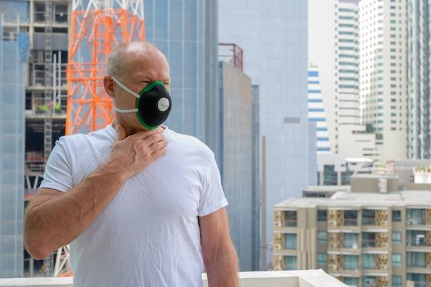 Man à l'aide d'un masque facial pour se protéger du smog de pollution en ville
