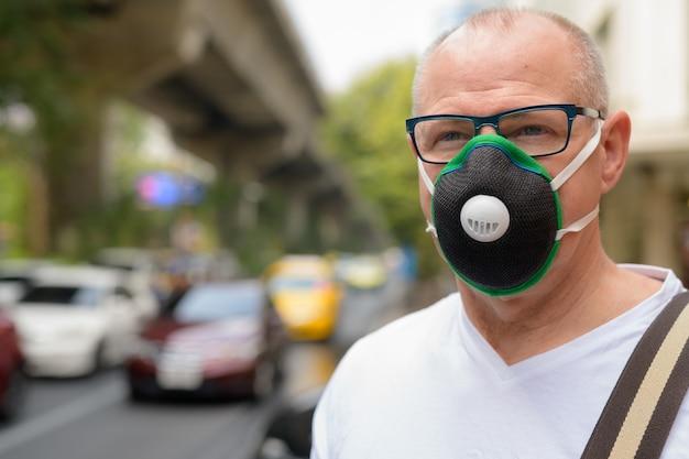 Man à l'aide d'un masque facial pour se protéger du smog de pollution