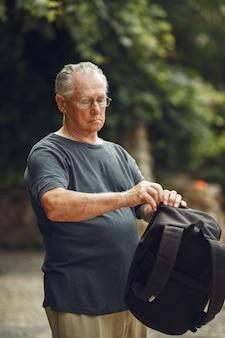 Man au parc d'été. grangfather avec un sac à dos.