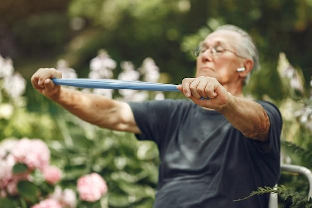 Man au parc d'été. grangfather utilisant un eraiser.