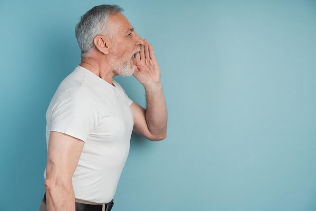 Man avec une barbe grise se tient dans le profil d'appeler quelqu'un