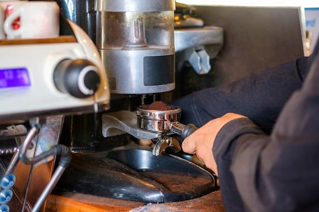 Man barista faisant de la poudre de mouture de café sur une machine à café