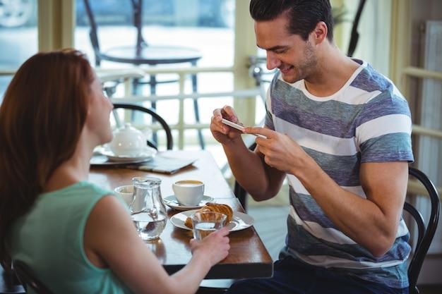 Man cliquant photo de croissant à partir du téléphone mobile en cafã ©