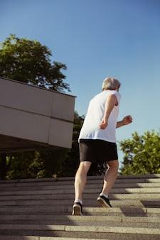 Man comme coureur avec brassard ou tracker de fitness dans la rue de la ville. modèle masculin caucasien pratiquant le jogging et les entraînements cardio le matin d'été. mode de vie sain, sport, concept d'activité.