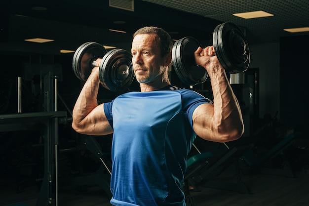 Man dans la cinquantaine, soulever des poids dans une salle de sport