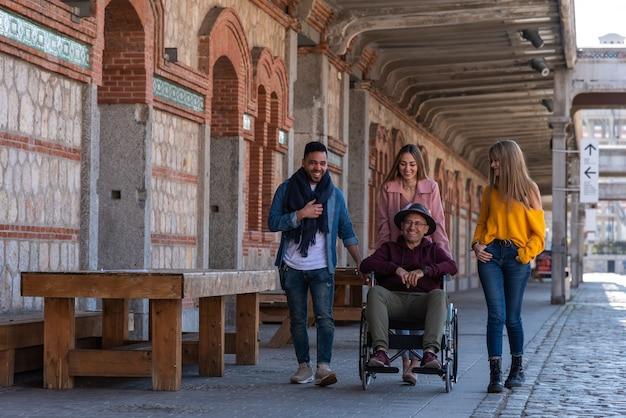 Man dans un fauteuil roulant accompagné de jeunes heureux