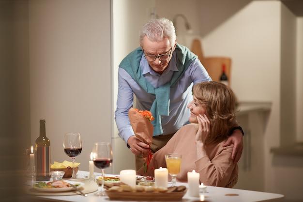 Man donnant un bouquet de fleurs à la femme pendant leur dîner le soir à la maison