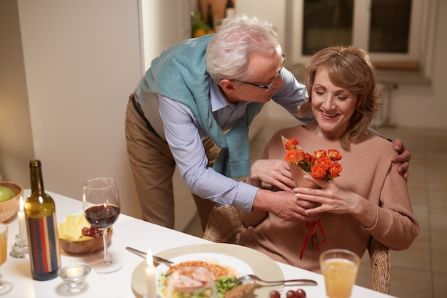 Man donnant des fleurs à sa femme et la félicitant pour leur anniversaire pendant le dîner