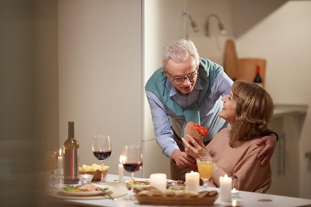 Man donnant des fleurs à sa femme lors de leur dîner romantique dans la cuisine