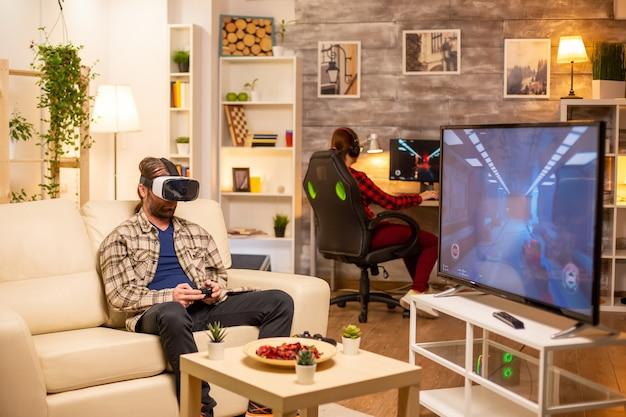 Man gamer utilisant un casque vr pour jouer à des jeux vidéo dans le salon tard dans la nuit