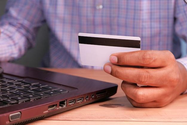 Man hands holding carte de crédit et à l'aide du clavier shopping en ligne, de haut en bas