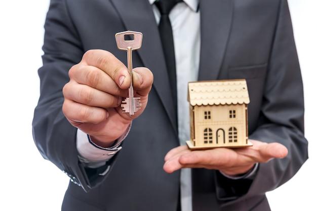 Man holding key et modèle de maison en bois