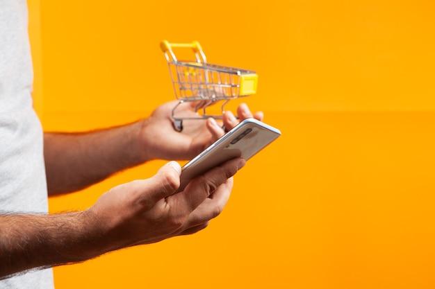 Man holding phone et panier sur fond orange