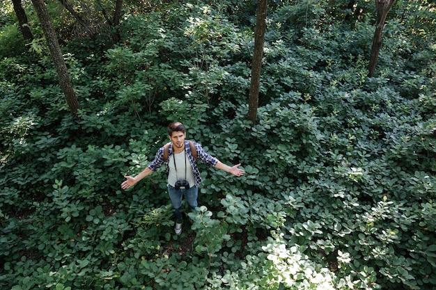 Man in forest avec jumelles et sac à dos