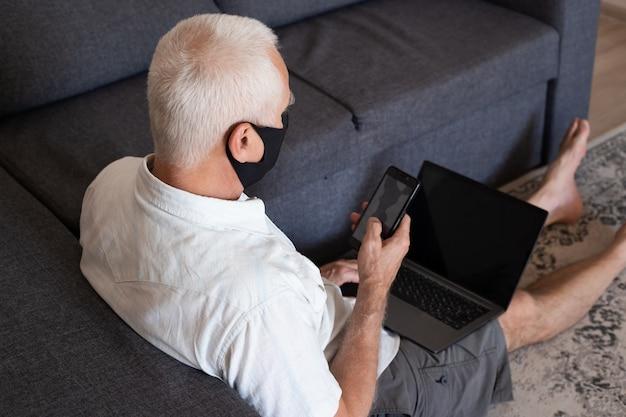 Man in masque médical travaillant à la maison sur son ordinateur portable calculer