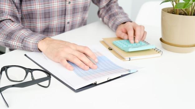 Man in office derrière table working on laptop