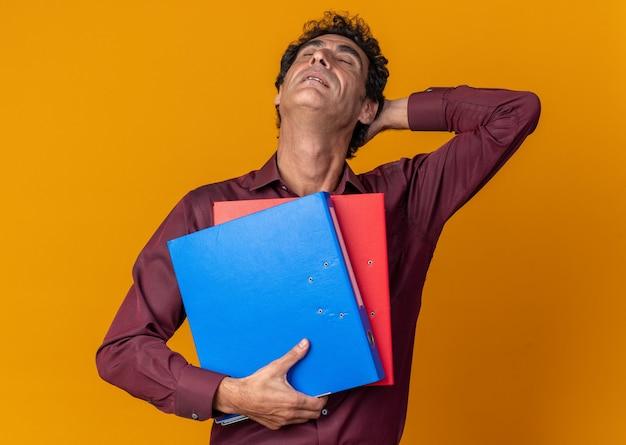 Man in purple shirt holding dossiers loking fatigué et surmené debout sur fond orange
