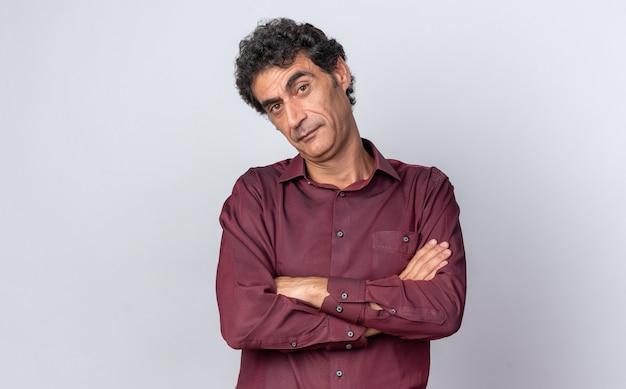 Man in purple shirt looking at camera avec expression sceptique avec les bras croisés debout sur fond blanc
