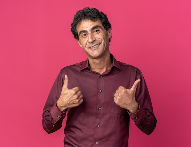 Man in purple shirt looking at camera heureux et positif souriant montrant gaiement les pouces vers le haut debout sur rose