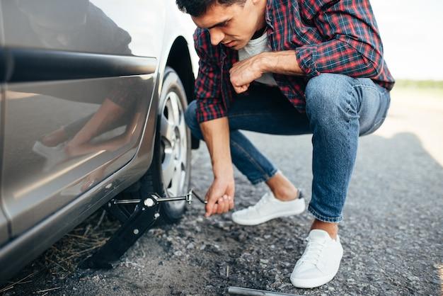 Man jack up voiture cassée, remplacement de roue. véhicule avec pneu crevé sur le bord de la route