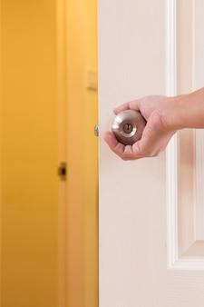 Man main tenant la poignée de porte